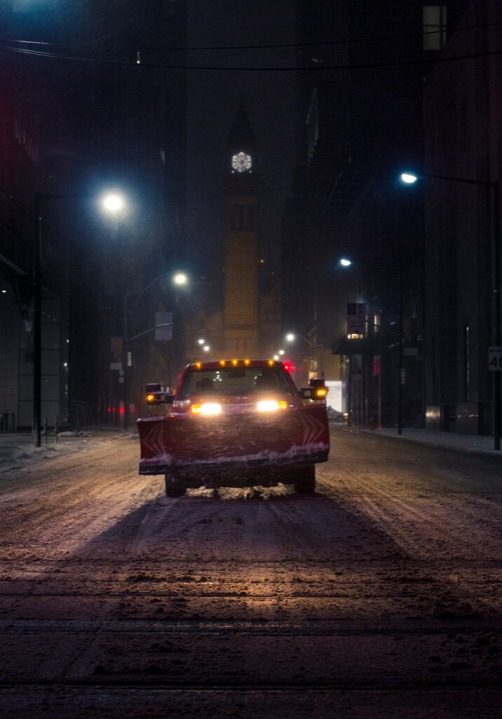 Photo Of A Snow Plow Truck In The Middle Of The Road In A City At Night